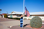 Lyn Baker raises the American flag outside of her father's home at 9626 Glen Oaks Circle in Sun City, Arizona March 13, 2010. Lyn's mother passed-away in December and moved in with her father to keep him company. 2010 marks the 50th anniversary of Sun City, the first planned retirement city in the United States.