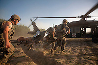 US Army soldiers load a wounded soldier onto a waiting medevac helicopter from Charlie Company, Sixth Battalion, 101st Aviation Regiment in the middle of a firefight near Kandahar. The wounded soldier had shrapnel wounds from a mortar fired at his position.