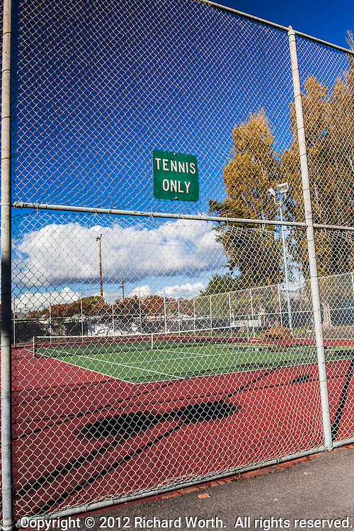 """The sign says, """"TENNIS ONLY"""", but there is much more to see.  Shadows and lines, clouds and sky.  Trees and utility poles.  And that fence.  That chain link fence.  A virtual, visual sieve of steel diamonds.."""