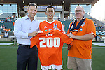 31 May 2014: Carolina's Kupono Low (center) is presented with a ceremonial jersey commemorating 200 appearances for the team by team president Curt Johnson (left) and founder of the supporters group Jarrett Campbell (right). The Carolina RailHawks played the Tampa Bay Rowdies at WakeMed Stadium in Cary, North Carolina in a 2014 North American Soccer League Spring Season match. Carolina won the game 2-0.