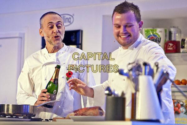 Michel Roux Jr.BBC Good Food Show London 2012, Olympia, Kensington, London, England..November 10th 2012.half length white chef jacket mouth open bottle champagne wine alcohol cook cooking poppy stubble beard facial hair  .CAP/MM/PP.©Mike Mustard/PP/Capital Pictures