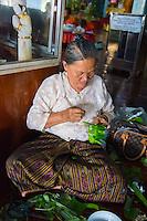 Thailand, Mae Hong Son. Wat Chong Klang Buddhist Monastery. Women preparing flower arrangemenst.
