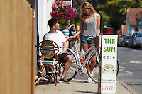 Zoe talking to Sam outside cafe, holding Charge Decanter bicycle .   Sunninghill, Berks.    July   2013.      pic copyright Steve Behr / Stockfile