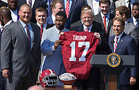 United States President Donald J. Trump receives a jersey from team members during the welcoming ceremony of the 2017 NCAA Football National Champions: The Alabama Crimson Tide to the White House in Washington, DC, March 10, 2018. <br /> CAP/MPI/RS<br /> &copy;RS/MPI/Capital Pictures