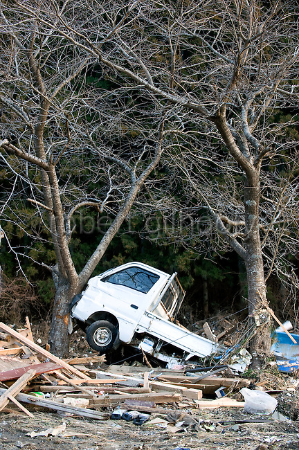 A small truck that was swept inland by the tsunami that followed the March 11 magnitude 8.8 quake remains stuck between to trees in the coastal town of Minami Sanriku Town, Miyagi Prefecture, Japan on 13 March, 2011. Some 10,000 people out of the town's population of  17,666 are reported as missing. Photographer: Robert Gilhooly