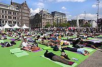 Nederland  Amsterdam - 2019.   Relaxen op de Dam. International Day of Yoga. Internationale Yogadag op de Dam in Amsterdam. Uitrusten na een reeks oefeningen.  Foto mag niet in negatieve / schadelijke context gepubliceerd worden.   Foto Berlinda van Dam / Hollandse Hoogte