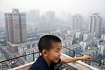 XIAN, CHINA - JUNE 3: Tao Tao, age 9, sits on the top of a high-rise building on June 3, 2007 in central Xian, China. He stays in a penthouse in the building with his parents. Many high-rise building has risen the last years in this city of about 3,3 million inhabitants. It is the capital of Shaanxi province in China. It was the eastern terminus for the Silk Road and the location for the Terracotta Army during the Qin Dynasty. Its history dates back more than 3,100 years. (Photo by Per-Anders Pettersson)..