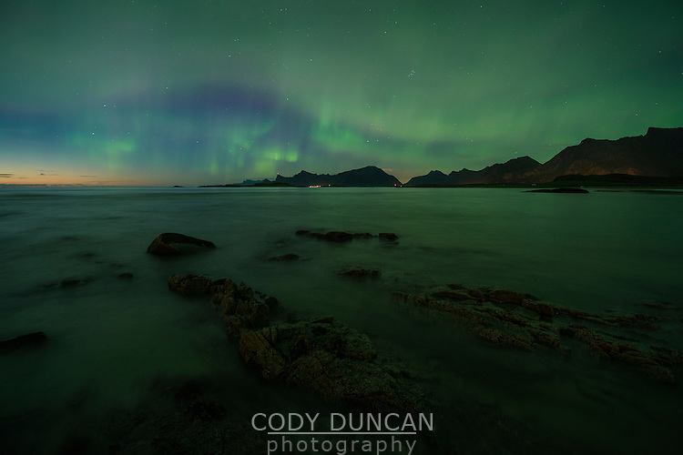 Northern lights fill sky over coastal mountains from Ytresand beach, Moskenesøy, Lofoten Islands, Norway