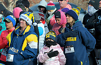 NWA Democrat-Gazette/DAVID GOTTSCHALK Mary Downar Patterson (center), 9, of Carson City, NV., listens to the National Anthem with other bundled up runners Monday, January 1, 2017, before the start of the 4th Annual Black Eyed Pea New Year's Day Run to run either the 5k or 10K course in Fayetteville. The race, organized by Doug and Pauline Allen, is free with all donations acquired going to the Fayetteville High School Cross Country teams. Snacks at the race included black eyed peas and cornbread.