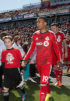 30 March 2013: Toronto FC midfielder Reggie Lambe #19 with a player escort leads Toronto FC onto the pitch during the opening ceremonies in an MLS game between the LA Galaxy and Toronto FC at BMO Field in Toronto, Ontario Canada..The game ended in a 2-2 draw..