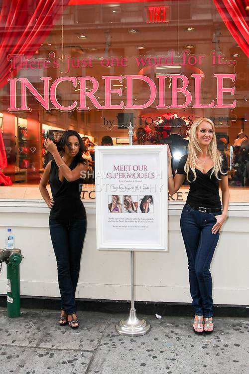 "Janelle and Irina pose with sign during the ""Incredible by Victoria's Secret"" launch at the Victoria Secret SOHO Store, August 10, 2010."
