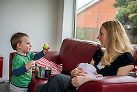 A woman sitting on a sofa breastfeeding her 2 month old baby while interacting with one of her older sons who is playing with a saucepan. He is howing her a ball.<br /> <br /> Hampshire, England, UK<br /> 10/02/2013