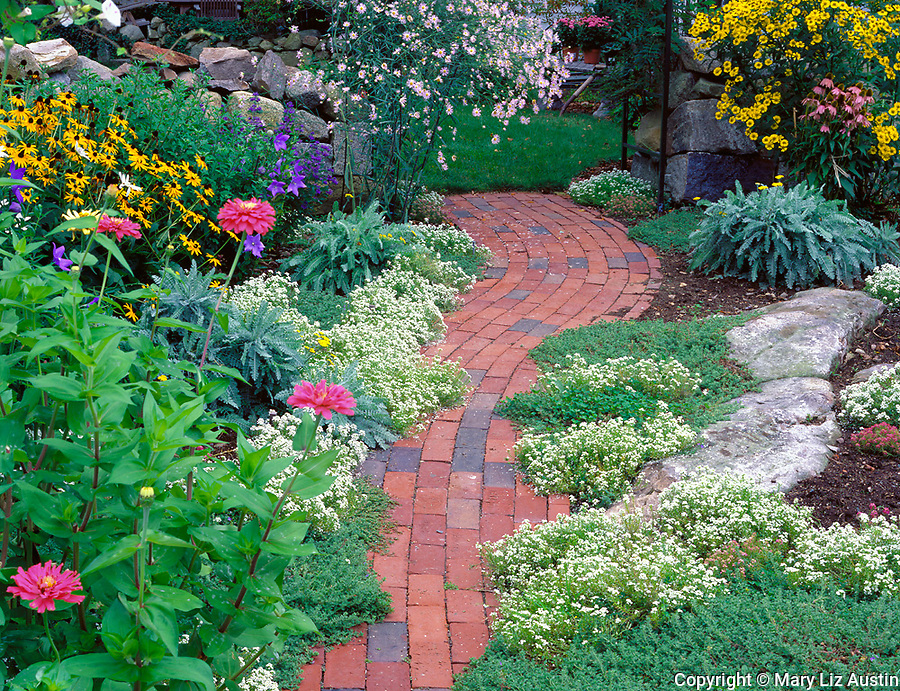 Rockport, Cape Ann, MA<br /> Summer flowers boarder a brick pathway in a Rockport garden
