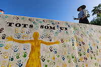"Spain. Balearic Islands. Minorca (Menorca). Mahon. The parade of the Giants in the ""Festes de la Mare de Déu de Gràcia"" during the traditional summer festival. On the wall, a painting of the shape of a person with both arms wide open and colorful hands prints. The words in catalan language mean "" We are all one"". Maó (in Catalan) and Mahón (in Spanish), written in English as Mahon, is a municipality, the capital city of the island of Menorca, and seat of the Island Council of Menorca. The city is located on the eastern coast of the island, which is part of the autonomous community of the Balearic. In Spain, an autonomous community is a first-level political and administrative division, created in accordance with the Spanish constitution of 1978, with the aim of guaranteeing limited autonomy of the nationalities and regions that make up Spain. 7.09.2019 © 2019 Didier Ruef"