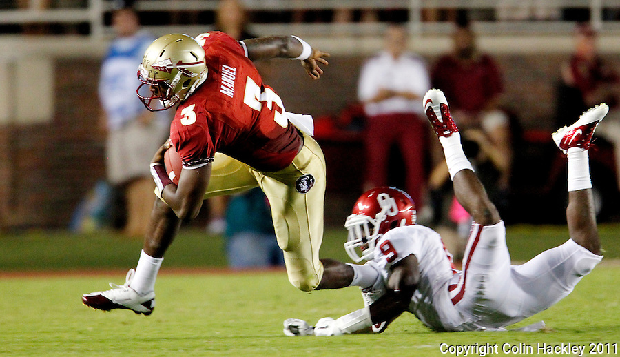 TALLAHASSEE, FL 9/17/11-FSU-OU091711 CH-Florida State's EJ Manuel is tripped up by Oklahoma's Gabe Lynn during first half action Saturday at Doak Campbell Stadium in Tallahassee. .COLIN HACKLEY PHOTO