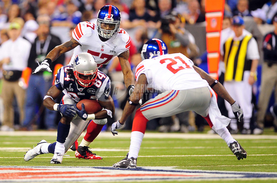 Feb 5, 2012; Indianapolis, IN, USA; New England Patriots wide receiver Deion Branch (84) is tackled by New York Giants strong safety Kenny Phillips (21) and middle linebacker Jacquian Williams (57) during the first half of Super Bowl XLVI at Lucas Oil Stadium.  Mandatory Credit: Mark J. Rebilas-