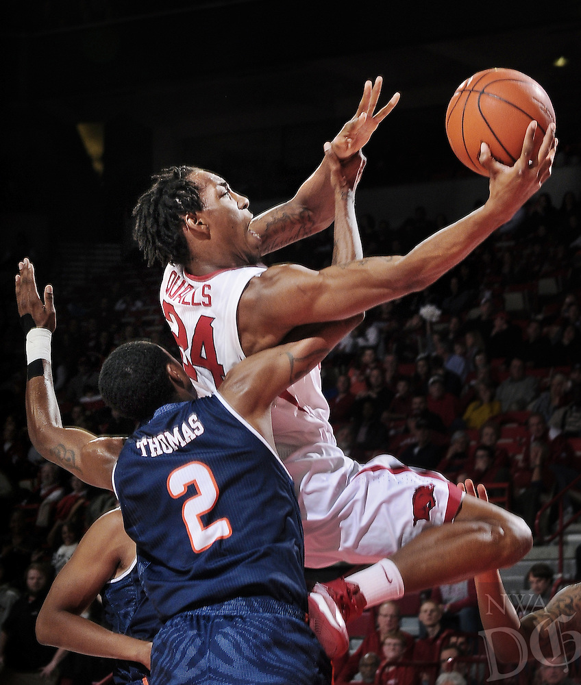 STAFF PHOTO BEN GOFF -- 01/04/14 -- UTSA's Hyjii Thomas attempts to block as Arkansas's Michael Qualls makes a shot during the first half of the game in Bud Walton Arena in Fayetteville on Saturday January 4, 2013.