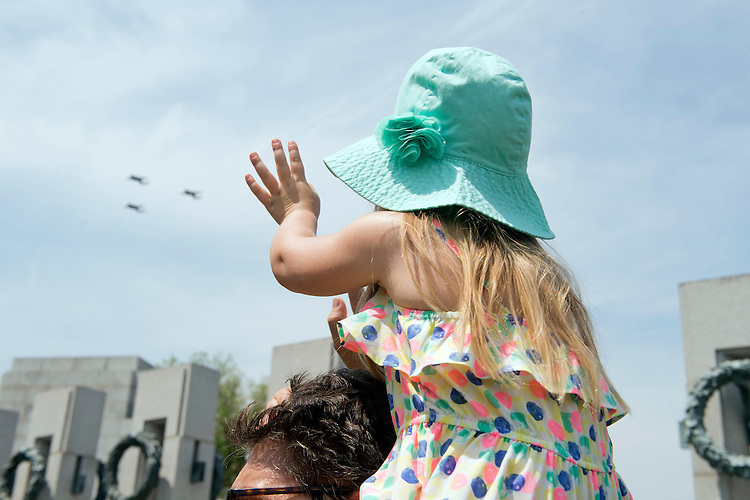 UNITED STATES - MAY 8: Sloan Mcihalski, 3, of Odenton, Md., waves to World War II era aircraft as they fly over the World War II Memorial on the Mall to commemorate the 70th anniversary of the victory in Europe, known as VE Day, May 8, 2015. (Photo By Tom Williams/CQ Roll Call)