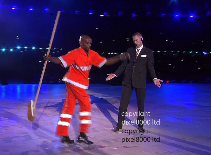 Olympics 2012 - BBC Coverage.Closing ceremony..Britain represented by officious security guard as Brazil does its bit....street cleaner Renato Sorriso, who is practising Samba steps. A security guard tries to remove him as a carnival parade invades...Sorriso found fame in 1997 when instead of sweeping the floor of the Sambodrome, he started to dance...Picture by Pixel8000 07917221968