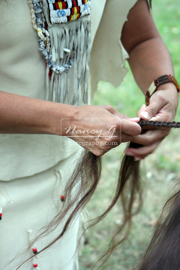 A Native American Indian woman braiding a childs hair