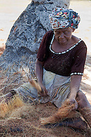 Kizimkazi, Dimbani, Zanzibar, Tanzania.  Woman Beating Coconut Husks to Produce Coir, to Make Ropes.