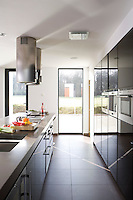 In the kitchen light floods in from floor-ceiling windows and a glass door leading to the extensive grounds