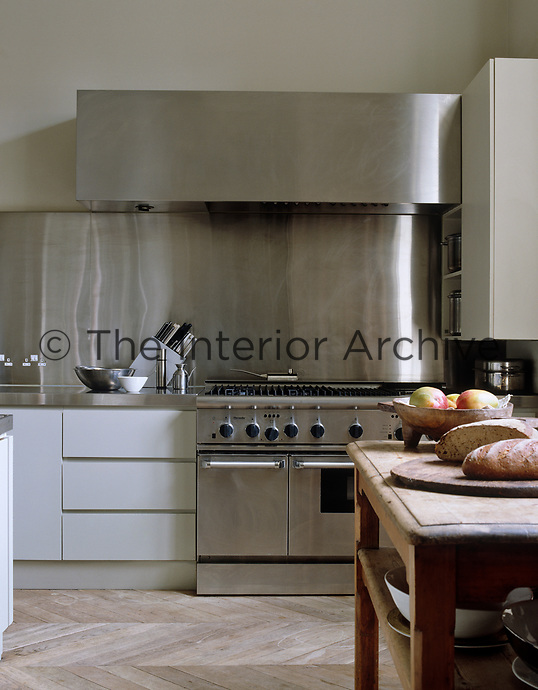 The industrial dual-fuel range is set against a substantial splashback of stainless steel and housed beneath a large extractor in this contemporary kitchen
