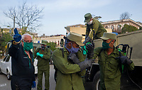 HAVANA, CUBA - April 15: Cuban soldiers wearing face masks get ready to disinfect sidewalks and streets in downtown in Havana, Cuba, on April 15, 2020. The military soldiers carry out a disinfection process in the city, applicable in parks, commercial areas, atriums, transportation stations and general public meeting places  decreed by the Government to contain the expansion of COVID. 19. (Photo by Eliana Aponte/VIEWpress)
