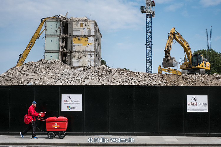 Postal worker with a high capacity trolley.  Demolition of  Gloucester House, South Kilburn Estate, London Borough of Brent.