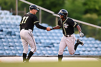 Omaha Storm Chasers outfielder Melky Mesa (22) is congratulated by manager Brian Poldberg (27) after hitting a home run during a game against the Nashville Sounds on May 19, 2014 at Herschel Greer Stadium in Nashville, Tennessee.  Nashville defeated Omaha 5-4.  (Mike Janes/Four Seam Images)