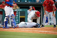 Syracuse Chiefs trainer Eric Montague checks on third baseman Jacob Wilson (19) after getting hit in the head by pitcher Sean Reid-Foley (not shown) during a game against the Buffalo Bisons on July 6, 2018 at Coca-Cola Field in Buffalo, New York.  Manager Randy Knorr (40) looks on.  Buffalo defeated Syracuse 6-4.  (Mike Janes/Four Seam Images)