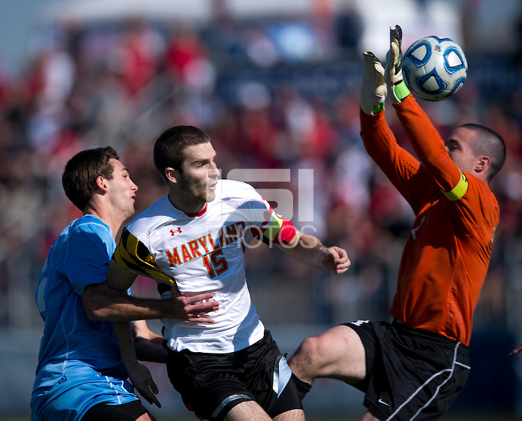 Patrick Mullins (15) of Maryland collides with Jonathan Campbell (2) of North Carolina as the ball goes over the gloves of Scott Goodwin (1) of North Carolina during the game at the Maryland SoccerPlex in Germantown, MD. Maryland defeated North Carolina, 2-1,  to win the ACC men's soccer tournament.