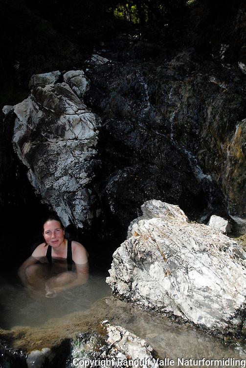 Dame bader i varm kilde. Lake Sumner Forest park, New Zealand. ---- Woman taking a bath in a hot spring along the Harper Pass Route. Lake Sumner Forest park, New Zealand.