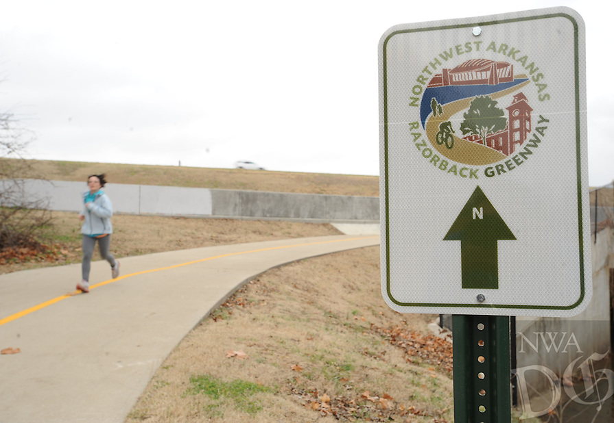 NWA Media/ANDY SHUPE - A runner makes her way south along the Scull Creek Trail, a section of the Northwest Arkansas Razorback Greenway, Sunday, Dec. 21, 2014, after passing through a tunnel beneath the Fulbright Expressway in Fayetteville. The greenway is a regional trail system that connects Northwest Arkansas.