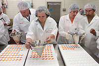 Students in a two-week candy-making class, the annual Resident Course in Confectionary Technology run by the College of Agriculture and Life Sciences, practice making &quot;gummies&quot; and &quot;jellies&quot; by funneling heated gelatin into starch molds to cool. Professional candy-makers from around the world come to Madison to polish their skills on (and polish off) hundreds of pounds of jelly beans, fudge, caramel, gum, nougats, and other candies.<br /> <br /> Client: University of Wisconsin-Madison<br /> &copy; UW-Madison University Communications 608-262-0067<br /> Photo by: Michael Forster Rothbart<br /> Date:  6/05   File#:  D100 digital camera frame 7412
