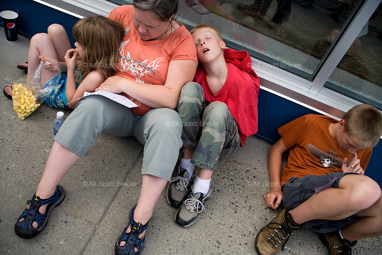 People rest on a sidewalk during Evel Knievel Days in Butte, Montana, USA.
