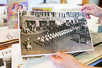 NWA Democrat-Gazette/CHARLIE KAIJO Monte Harris, adult program presenter of the Rogers Historical Museum, holds an image of a homecoming parade showing the Rogers High School Pep Club marching in front of the old Lane Hotel, which is now Haas Hall on Poplar Street, Friday, March 30, 2018 at the Rogers Historical Museum Education Annex in Rogers. <br /><br />Collectors from the group Finders Keepers share antiques with each other. They will hold meetings on the last Friday of every month from March until September at the Rogers Historical Museum Education Annex until the Rogers Historical Museum completes its expansion. Attendees may share antiques but the group does not provide appraisals for items.