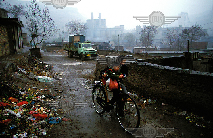 ©Mark Henley/Panos Pictures..China, Shaanxi, Tongchuan..Pollution & poverty. Mother and her child in grim landscape,  in a town dominated by decaying state-owned industry.