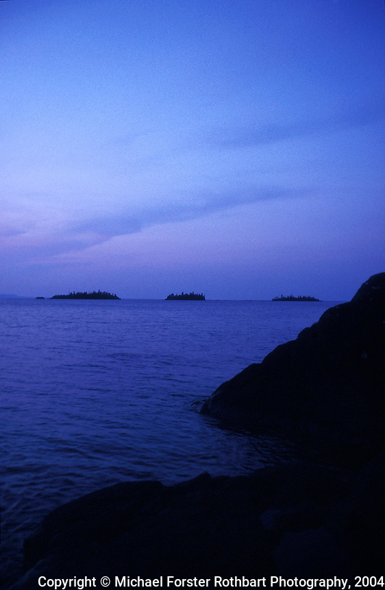 View at dusk of Lake Superior and three small islands off the north shore of Isle Royale, seen from near Todd Harbor campsite, in Isle Royale National Park, Michigan.<br /> <br /> &copy; Michael Forster Rothbart<br /> www.mfrphoto.com <br /> 607-267-4893 o 607-432-5984<br /> 5 Draper St, Oneonta, NY 13820<br /> 86 Three Mile Pond Rd, Vassalboro, ME 04989<br /> info@mfrphoto.com<br /> Photo by: Michael Forster Rothbart<br /> Date:  7/2004    File#:  color slide