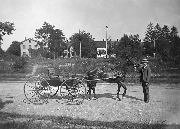 A man proudly poses with his horse and carriage. Circa 1900.