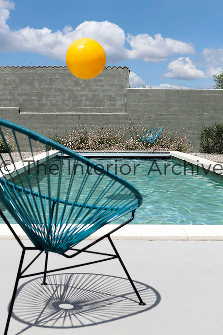 A pair of Acapulco garden chairs in turquoise reflect the colour of the outdoor swimming pool