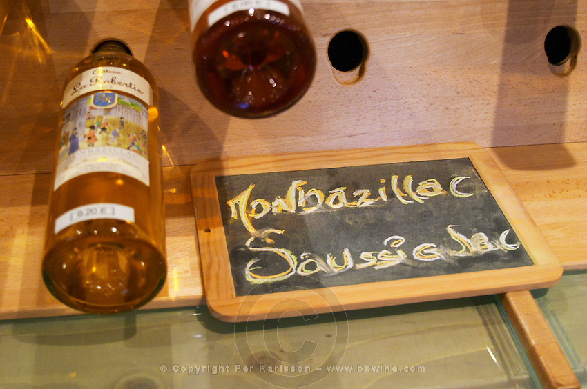 Golden yellow bottles of sweet white Bergerac and Monbazillac wine on display at the Maison de Vin in Bergerac, the House of Wine, chalkboard saying Monbazillac and Saussignac Bergerac Dordogne France
