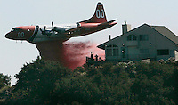 A firefighting airtanker drops fire retardant very near homes along West Camino Cielo Road community, The Santa Barbara fire burned thousands of acres and triggered 1,700 homes to be evacuated.