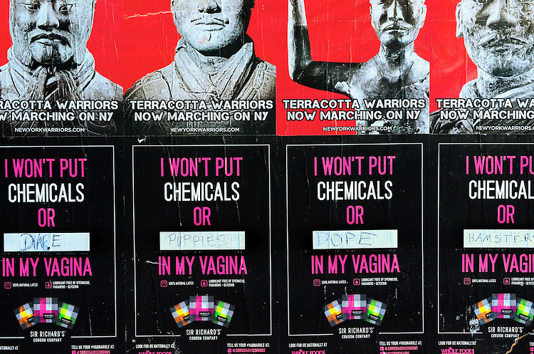 Different posters on the street advertising a brand of condoms and an exhibition of the terrcotta warriors. Manhattan, New York City.