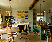 The large family kitchen has a handmade oak kitchen table, open fireplace and is decorated with the children's paintings