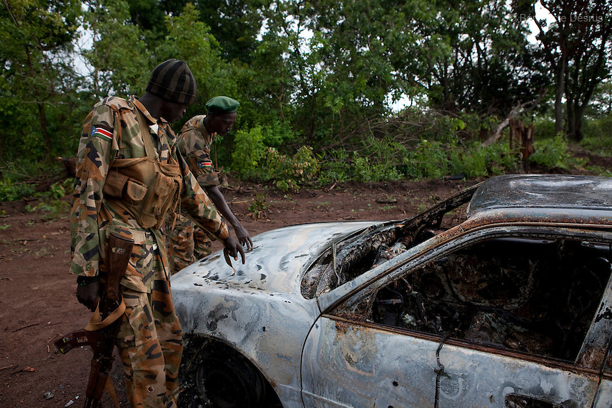 22 may 2010 - Western Equatoria State, South Sudan - An SPLA soldier shows the bullet holes in a car that was ambushed and burnt by the Lord's Resistance Army (LRA) on the road between Yambio and Tambura. The three victims were government officials in the State Ministry of Education: Mr. William Arkangelo Baabe, Mr. Gabriel Makana (49 years old) and Baraka Josefati (25 years old). The LRA has attacked a number of roads, villages, and clinics in the area over the last week pushing thousands of people to flee to larger towns for protection. Western Equatoria state has been rocked by LRA activities since 2006. Thousands of people have been forced from their homes as brutal attacks continue against the civilian population in the region and neighboring DRC and CAR. Photo credit: Benedicte Desrus