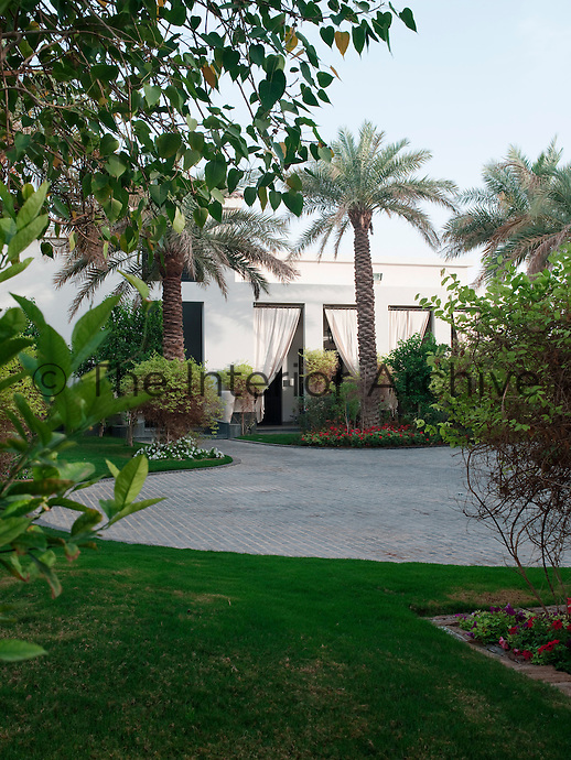 The driveway, paved with bricks and surrounded by manicured lawns, flowerbeds and palmtrees