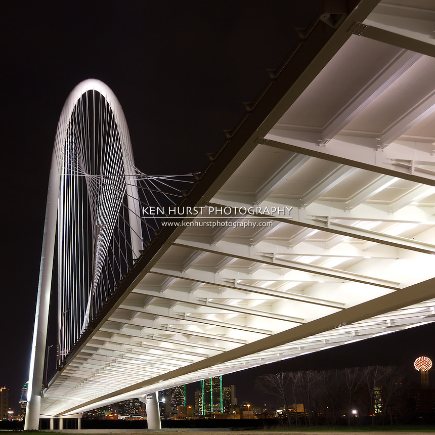The newly constructed (2012) Margaret Hunt Hill bridge, designed by Santiago Calatrava, with the night lights of Dallas, Texas in the background.