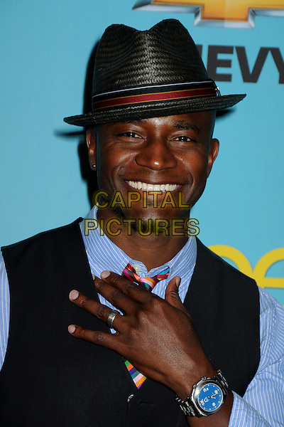 "TAYE DIGGS .Fox's ""Glee"" Spring Premiere Soiree held at Bar Marmont, West Hollywood, California, USA, .12th April 2010..portrait headshot hat red blue shirt tie striped waistcoat plaid checked check tartan hand smiling wrist watch .CAP/ADM/BP.©Byron Purvis/AdMedia/Capital Pictures."