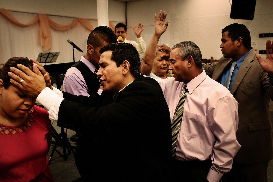 Central Falls, Rhode Island, July 15, 2012 - Pastor Narciso Romero prays over one of his congragants at Iglesia Pentecostal Unida. Churches and religious organizations are helping to fill some gaps and keeping the community together. Iglesia Pentecostal Unida hosts events several nights each week for its congregation. <br />
